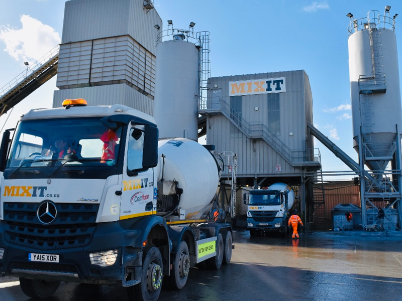 Concrete delivery via concrete mixer truck infront of the Mixit machinery for concrete blocks