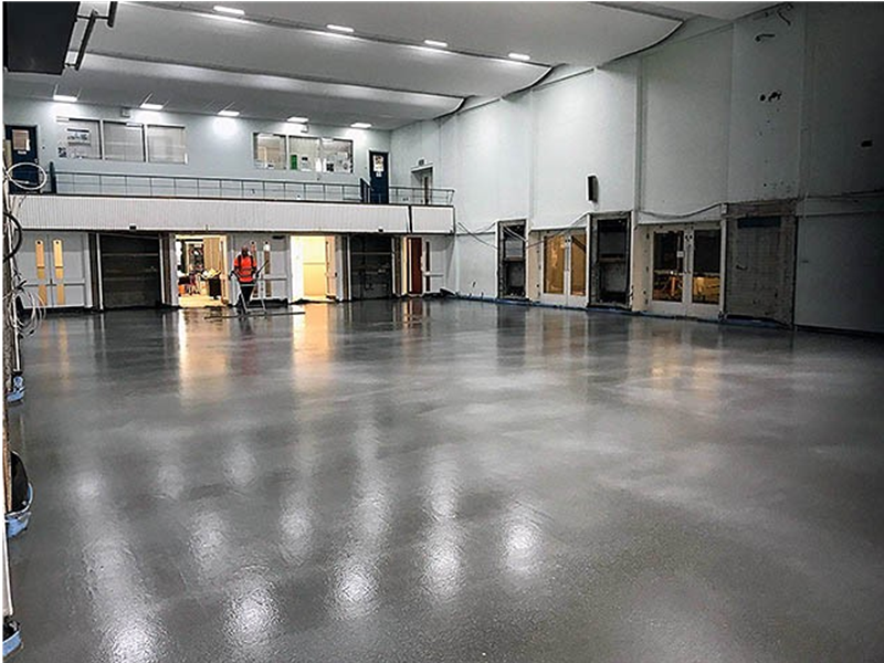 Large concrete floor screed in a medium sized warehouse while someone is flatening the floor